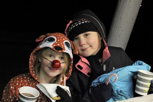 Two Children with Hot Cocoa Watching the Tree Lighting