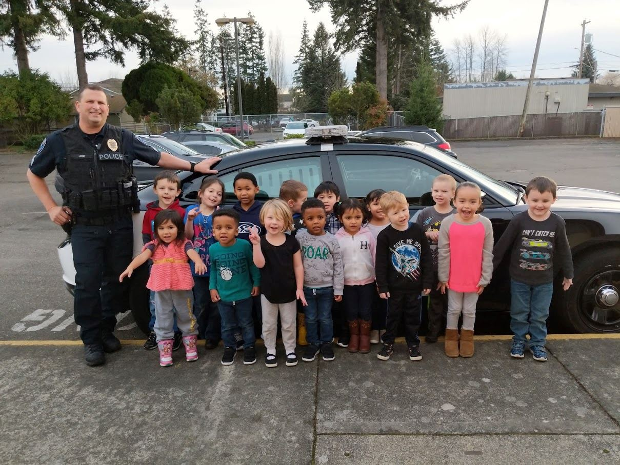 Sergeant standing with students in front of patrol car
