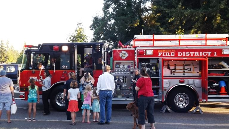 FD 1 at Families gathered around a red fire engine for a tour